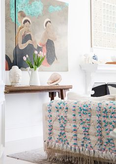 A wood console table in the living room styled with tulips and antique artwork across from a white sofa with an embellished throw blanket