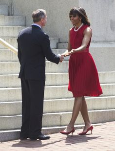Mrs. O wore a crimson pleated georgette crewneck dress by Michael Kors, previously seen on the cover of Parade magazine in 2011, here. Red patent pumps and a double strand of pearls completed the polished look.