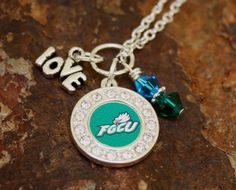 Show everyone you are proud to support your Florida Gulf Coast Eagles with this necklace. A FGCU Charms with rhinestones around it, a Love charm and green and blue Swarovski crystals make up this necklace. Florida Gulf Coast Beaches, Florida Gulf Coast University, University Dorms, Love Charms, Eagles, Washer Necklace, Swarovski Crystals, Bling, Road Trip