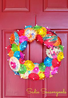 Drink Umbrella Wreath! Perfect for riding out the rest of summer- a burst of tropical colors from cocktail umbrellas / parasols make for a spectacular summer wreath!