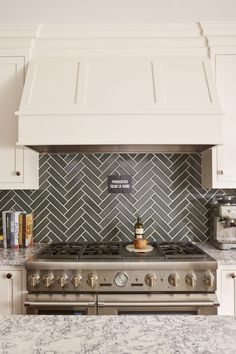 This classic herringbone tiles kitchen backsplash features a smokey handmade glaze, serving up a sophisticated contrast to the warm white cabinetry. Gray Kitchen Backsplash, Herringbone Backsplash, Kitchen Hoods, Backsplash Ideas, Herringbone Pattern, Cutting Edge Stencils, Patterned Kitchen Tiles, Dark Grey Kitchen, Fireclay Tile
