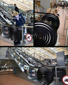 """Two handrails of an escalator look like enormous strings of liquorice that end up in an over-sized Liquorice Fruit Wheel."""