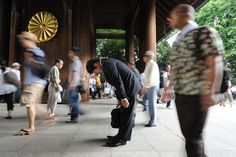 A salaryman stops in mid stride and bows before the gate of the Yasukuni Shrine in Tokyo as Japan commemorated the 67th anniversary of the nation's World War II surrender on August 15, 2012.