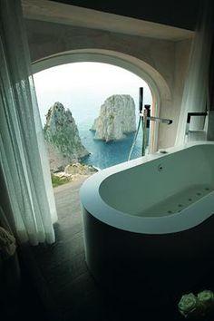 Hotel Punta Tragara in Capri, Italy, features awe inspiring views of the Faraglioni from the oversized bath of the Punta Tragara Art Suite.