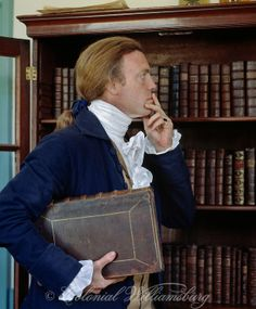 Searching for a book in the study. 18th Century scene at historic Colonial Williamsburg, Williamsburg, Virginia. Photo by David M. Doody