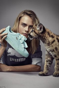 Feline fine: Posing with a baby puma, Cara's fellow model certainly threatens to steal the...