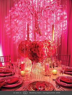 Silver manzanita branches draped with crystal garlands collared in red, coral and fuchsia roses.