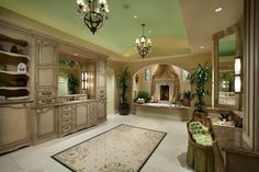 This enormous, traditional bathroom boasting a hot tub and fireplace defines luxury. A gorgeous, marble-topped vanity and ornate chandeliers accent the grandness of the space.