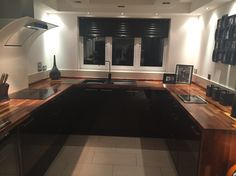 Black gloss kitchen with solid wood worktops.