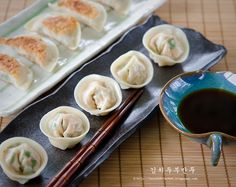 Add chopped kimchi into dumplings to make flavorful Korean tradition. These appetizing dumplings are made with kimchi, tofu, pork, and chives.