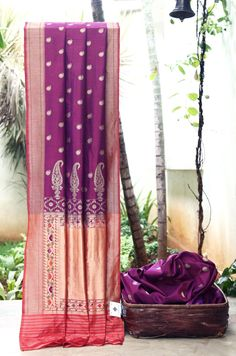 EXQUISITE PURPLE WITH A SHOT OF CHILLY RED BENERAS TUSSAR HAS PAISLEY ZARI BUTTAS ALL OVER. THE GOLD BORDER EXTENDED INTO PALLU GIVES THE SAREE GLOWING LOOK.