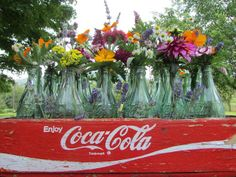 Flower  Arrangement with Old Coca-Cola Bottles in a Vintage Wooden Crate
