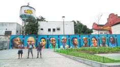 2016 Olympics ~ Rio street artists in front of the mural they created to mark the first-ever Refugee Olympic Team.