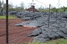 2014: The Year in Volcanic Activity - In Focus - The Atlantic  Lava flows on a dirt road past a protected utility pole, a result of the Kilauea Volcano eruption and lava flow. (FEMA/Kelly Hudson)