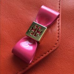 "Tory Burch Pink Bow/Equestrian Orange Wristlet 4""H x 6""L x 1""D Authentic. Brand new. Removable wrist strap. Top zip closure, exterior slip, snap flap pocket, 3 card slots. Stores phone, credit cards, etc. Hard to part w/ but willing to sell to a Tory Burch fan! Tory Burch Bags Clutches & Wristlets"