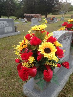 Cemetery vase using red roses, yellow sunflowers, yellow forsythia with red ribbon streamers. April 2016