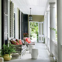 Style Guide: 60 Breezy Porches and Patios | Classic Charleston Porch | On this porch, or piazza, classic white wicker is dressed with zesty pillows.  | SouthernLiving.com
