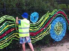 (fence weaving) desenhando em alambreado com fitas plásticas coloridas