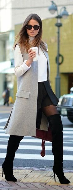 Pair a grey sleeveless coat with a black skater skirt to effortlessly deal with whatever this day throws at you. Add black suede thigh high boots to your look for an instant style upgrade.