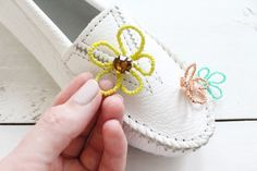 Step 7 | Play with the arrangement of the flowers on each shoe.  I kept my placement random for a playful feel.  Add a dot of E6000 glue to the back of the rhinestone flowers and hold in place on the moccasins to stick. Allow the glue to cure overnight before wearing!