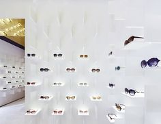 A combination of horizontal shelves, vertical fins and hidden LEDs dramatically illuminates the glasses within Bolon Eyewear's first flagship store, designed by Ippolito Fleitz Group with Pfarré Lighting Design.