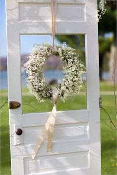 Baby's breath wreath on door at wedding ceremony. Captured By: Stephanie N. Baker ---> http://www.weddingchicks.com/2014/06/06/funky-finds-turned-into-surprising-centerpieces/