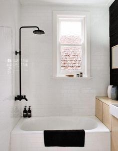 petite salle de bains en noir et blanc avec carrelage métro blanc et baignoire douche pratique