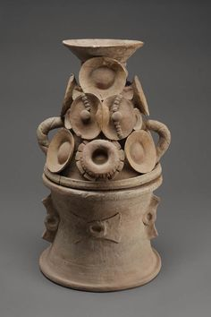 Hourglass-shaped base for a Maya Teotihuacan-style incense burner. Two flanges attached to opposite sides of the base are embellished with circular disks that may represent earflares Dated A.D. 400–550