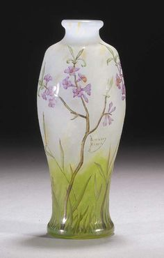 A DAUM ENAMELLED GLASS VASE - the clear glass internally mottled with white, yellow and green towards the base, etched and enamelled in shades of green, brown and pink with flowers, cameo mark Daum Nancy with a cross of Lorraine -- 20cm. high.