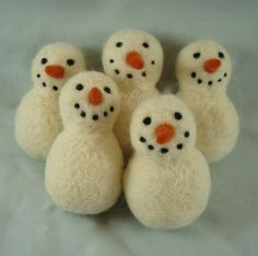 Adorable needle felted snowmen.  Would make nice ornaments for a Christmas tree or even tied to a gift