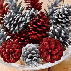 Bowl of colored pine cones for Christmas decoration or centerpiece - Lightly spray-paint half the cones in cheery cranberry, the rest in shimmery silver; display in a clear glass bowl. - bjl