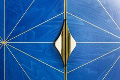 Detail from marquetry cabinet with blue dyed veneer and satin wood inlay with gold plated brass handles and door edging.