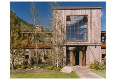 Exterior view of the entry during daylight.  A contemporary interpretation of traditional barn, log, and timber mountain homes.  Recycled wo...
