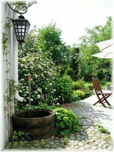 Gartengestaltung: Schöne Bepflanzung rund um das Regenfass