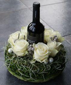 Fles rechtstaand verwerkt in een bloemstuk.