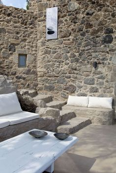 Melanopetra greek architecture with modern minimalist decoration using wood, stone, polished cement, and built-in furniture in white and earthy colors.