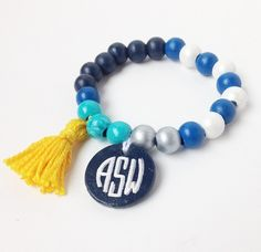 """Individually hand painted, hand crafted wooden beads with a hand painted wooden monogram charm and a cotton tassel.  *Details: -Approximately 7.5""""(designed to fit 6-6.75"""" wrist) -Individually hand painted beads and charm -Stretchy design for easily rolling on and off wrist  *Materials: el..."""