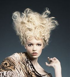 A long blonde curly wavy messy spikey quirky avant garde coloured hairstyle by Cutting Room Creative