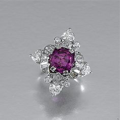 PINK SAPPHIRE AND DIAMOND RING Centring on a cushion-shaped pink sapphire weighing 5.09 carats within a scalloped mount set with tapered baguette, marquise-shaped and brilliant-cut diamonds, the cardinal points set with heart-shaped stones
