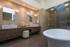 Contemporary Full Bathroom with Wall sconce, Skylight, limestone tile floors, European Cabinets, High ceiling, Vessel sink