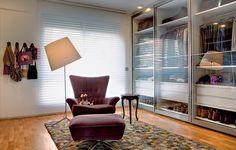 A área de vestir tem armários com portas de vidro deslizantes. Sobre o tapete da espanhola Nanimarquina, a poltrona e a mesinha dão o suporte ideal. Reforma da SAO Arquitetura