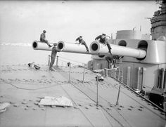 Gunnery scenes on board the battleship HMS Rodney. October 1940, at sea. Cleaning the big guns.