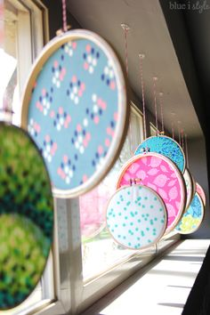SO BRIGHT & FUN! Add so fun punches of color for spring and summer by creating a window display of fabric filled embroidery hoops.