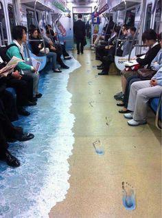 Quem entra nesse vagão do metrô de Seoul, na Coréia, se sente de férias :-) O adesivo colocado no chão imita uma praia, com direito à água do mar e pegadas na areia.