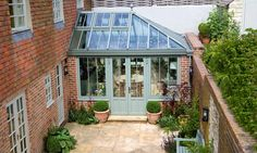 There's no reason to be limited by a small space. This M&L conservatory neatly tucks into the garden walls, extending the kitchen and dining area.