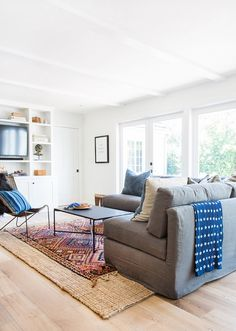 Cozy white living space with sectional and blue throw