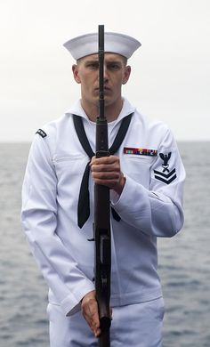 Gunner's Mate 2nd Class Nate Anderson renders honors during a burial at sea ceremony on elevator four aboard the Nimitz-class aircraft carrier USS John C. Stennis (CVN 74).