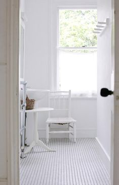 A white bathroom with simple wood furniture for a Scandinavian feel. See this full London home here at Sneak Peek: Jane Cumberbatch. #sneakpeek