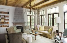 """The living room's calm, neutral palette lets the beauty of the wooded backyard shine through the large windows. """"Having all of the windows l..."""