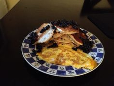 Breakfast of kings. Pancakes made with fresh Canadian blueberries (hand picked) topped with more blueberries topped with 100% real Canadian maple syrup. Complete with perfectly browned omelet with bonus bacon in the back hidden by the mountain of delici